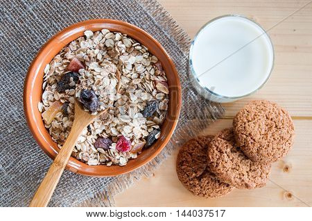 Serving Muesli Scattering Of Oat Cookies, Milk On Wooden Table