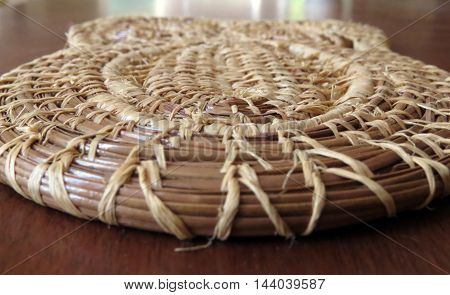 An owl-shaped coaster made of a jute and bamboo weave