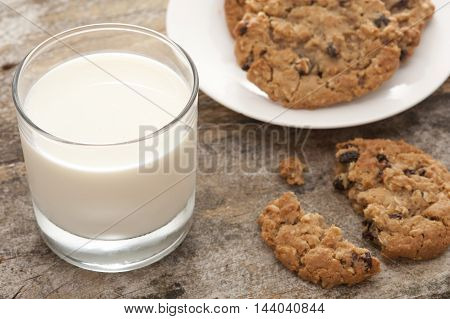 High Angle Close Up Still Life of Glass of Cold Refreshing Milk Beside Plate of Fresh Baked Cookies with Single Broken and Half Eaten Biscuit in Foreground
