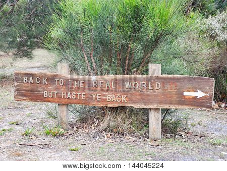 Wooden sign with short travel phrase in native bushland setting in Western Australia.