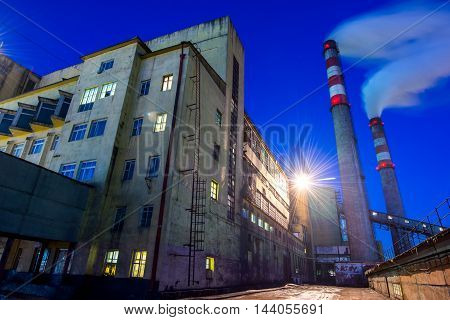 Coal powered plant and smoke stacks at night