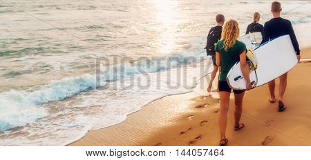 Bikini Girl Surfers Running Into The Sea With Surf Boards