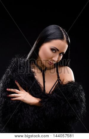 Young brunette lady in black dress posing on black background. Beautiful model with perfectr make-up in studio. Decollete.