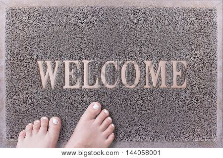 Welcome Door Mat With Female Feet. Friendly Grey Door Mat Closeup with Bare Woman Feet Standing. Welcome Carpet. Girl Feet with White Painted Toenails on Foot Scraper.