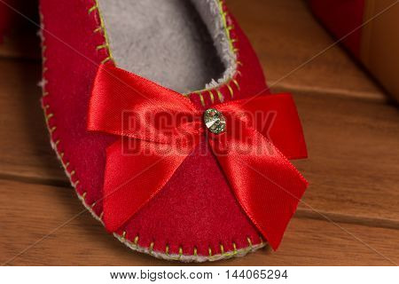 Close-up picture of a red house slipper on wooden floor. Beautiful red house slipper with red bow as a New Year or Christmas present or gift.