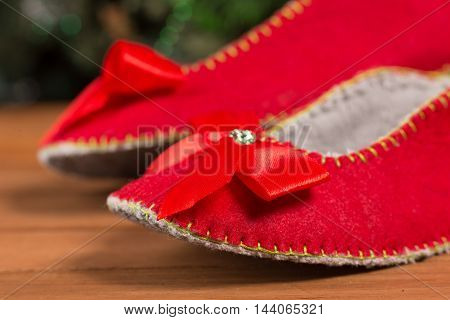 Christmas house slippers on the floor in bright house. Red houde slipper with red bows are warm and comfortable.