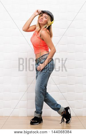 Beautiful hipster girl dancing in studio. Happy blond lady in jeans and jogging shoes traning modern dances isolated on white background.
