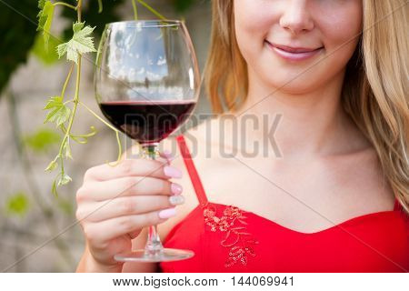Beautiful woman drinks red wine outdoor on a hot summer afternoon
