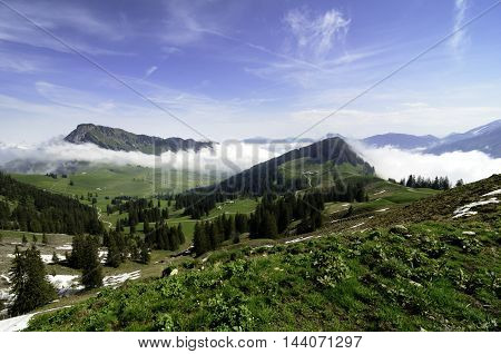 Beautiful morning in Swiss Alps with mountain tops clear sky and clouds