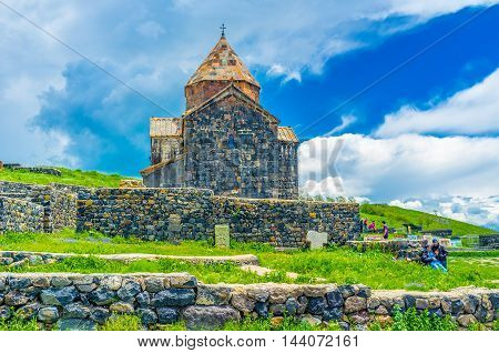 SEVAN ARMENIA - MAY 31 2016: The old Church of Holy Apostles of Sevanavank Monastery surrounded by stone fence on May 31 in Sevan