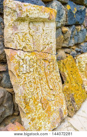 The old broken white khachkar covered with the yellow lichen Sevanavank Monastery Sevan Armenia.