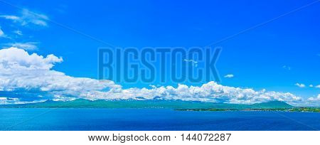 The bright blue waters of Sevan lake surrounded by the snowbound mountains holding the fluffy clouds Sevan Armenia.