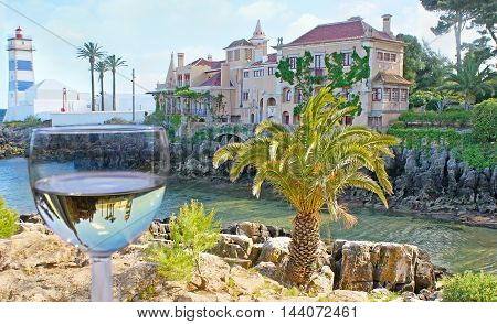 The scenic Santa Marta lighthouse and the Villa of Santa Maria on the rocky bay reflect in glass of white wine Cascais Portugal.