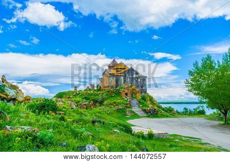 The stone church of Hayravank Monastery covered with bright orange lichen located on the gentle hill on the bank of Sevan Lake Armenia.