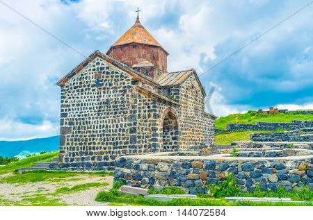 The St Astvatsatsin Church of Sevanavank Monastery built of black stone with the red dome located on the top of the hill on Sevan Peninsula Armenia.