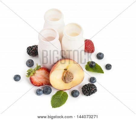 Drinking yogurts in bottles fresh peach and berries on white background