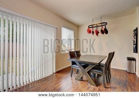 Dining Room With Wooden Table Set And Exit To The Back Yard.