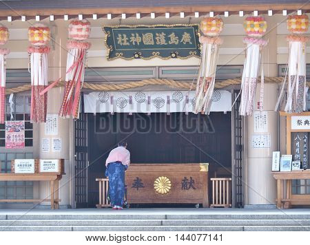 HIROSHIMA, JAPAN - JULY 18, 2016: Woman dressed in traditional dress called Kimono praying in Hiroshima Gokoku Shrine. In 1945, this shrine was destroyed by the atomic bombing, and was rebuilt in 1965.