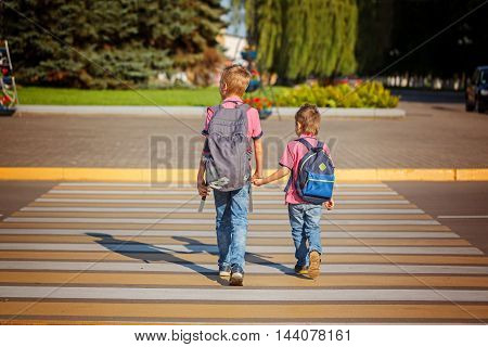 Two boys with backpack walking holding on warm day on the road. Back view.