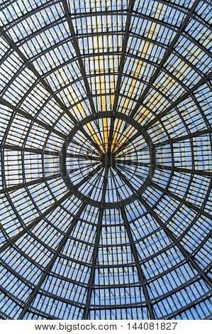 Multiple glass windows as part of domed ceiling. Vertical format with metallic and glass dome structure detail under blue sky.