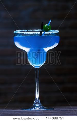 Cocktail Blue Lagoon On A Dark Background . Beautifully Illuminated .standing On The Bar .
