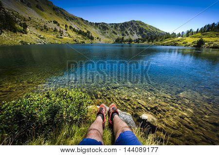 Lake And Legs During Mountain Hiking At Pyrenean Mountain