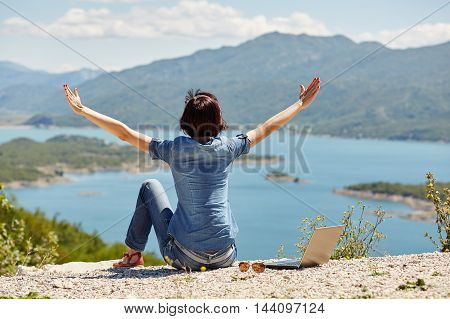 Beautiful Young Freelancer Woman Using Laptop Sitting On The Lake.happy Smiling Girl Working Online.