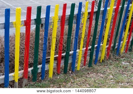 Closeup of a colorful garden fence of wood - old fence revitalized by vivid colors