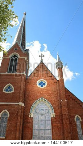 a brick church and steeple against a blue sky