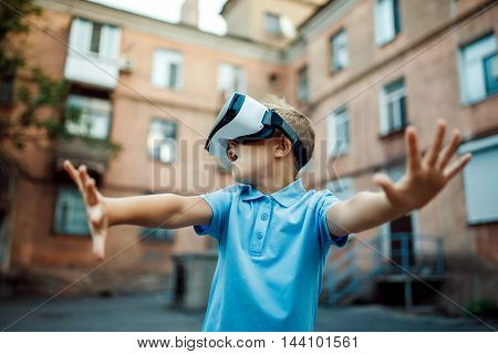 Fascinated little boy using VR virtual reality goggles. outdoor