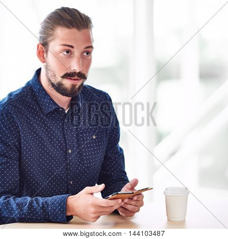 square image of trendy hipster holding a mobile phone in his hands, busy looking up but not into the camera with ato go coffee on the table in front of him.