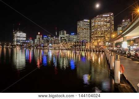SYDNEY, AUSTRALIA - APRIL, 2016 : People sitting at harbourside promenade with view of Sydney city skyline at night, Cockle Bay Wharf in Sydney, Australia on April 19, 2016.