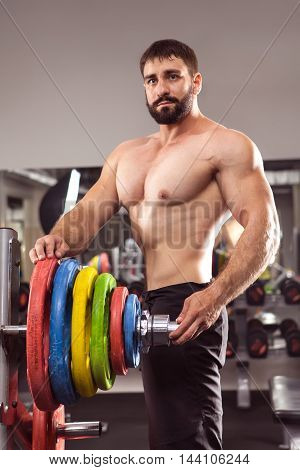 Powerful Man With Muscular Build Is Standing Near The Barbell In The Gym.