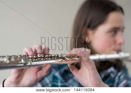Teenager playing flute - Copy Space and blurred person