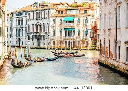 Venice, Italy - May 18, 2016: Gondoliers sail on gondolas full of tourists in the water canal in Venice. Gondola is a traditional venetian boat and famous tourist attraction.