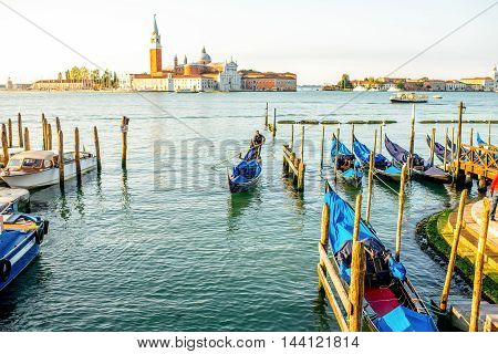 Venice, Italy - May 18, 2016: Gondolier sail on gondola in lagoon with San Georgio Maggiore island on the background in Venice.
