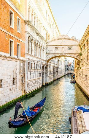 Venice, Italy - May 18, 2016: Gondolier sail on gondola in water canal near the bridge of Sighs in Venice.