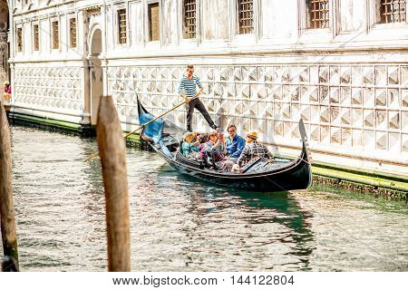 Venice, Italy - May 18, 2016: Gondolier sail on gondola full of tourists on the narrow water canal in Venice. Gondola is a traditional venetian boat and famous tourist attraction.