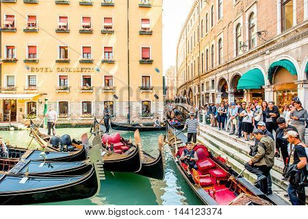 Venice, Italy - May 18, 2016: Gondoliers waiting for clients near crowded with tourists street. Sailing in godolas is a most popular tourist attraction in Venice