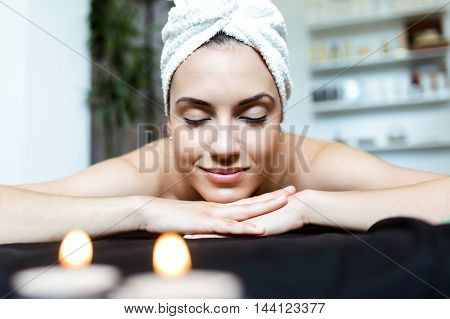 Portrait of pretty young woman enjoying massage at beauty spa.
