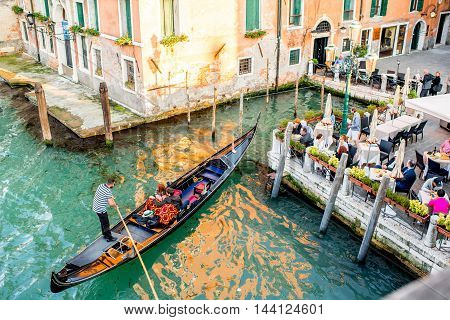 Venice, Italy - May 18, 2016: Gondolier park gondola with tourists near restaurant terrace in Venice. Gondola is a traditional venetian boat and a famous tourist attraction.