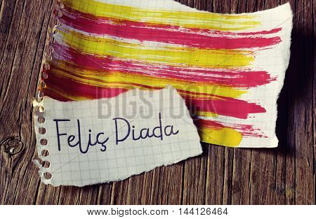 the text Felic Diada, Happy National Day of Catalonia in Catalan written in a piece of paper, and the Catalan flag painted in another piece of paper, on a rustic wooden surface