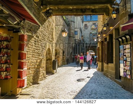 MONT SAINT-MICHEL, FRANCE - MAY 04, 2014: Visitors walk on medieval streets of Mont Saint-Michel France