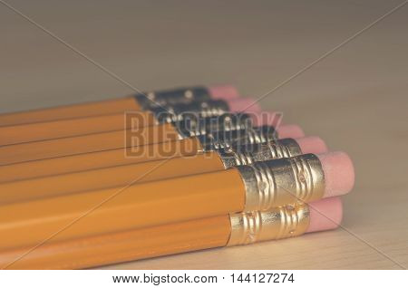 Image of many pencils stacked together on a desk
