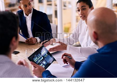 Business meeting between four upper management board members in the new modern office conference room with technology integrated in the form of an electronic tablet.