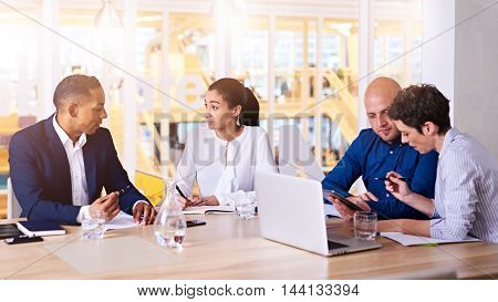 Group of business executives meeting with each other at sunrise early in the morning in their bright, modern conference room