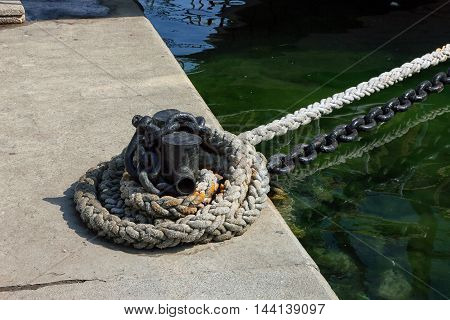 black metal iron mooring bollard with mooring line and chain and green sea water