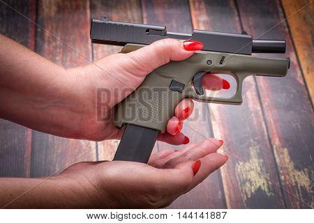 Woman Loading Handgun Magazine on wood Surface