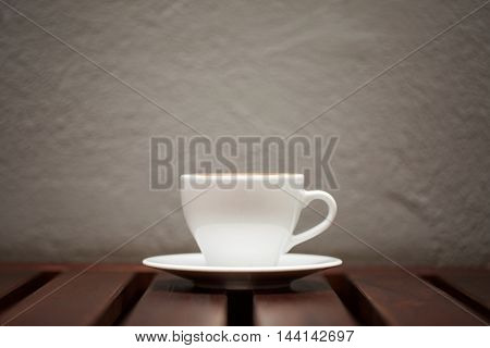 Wtite cup of coffee on wooden table and grey wall background.