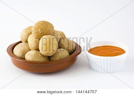 Canarian potatoes (papas arrugadas) with mojo sauce isolated on white background